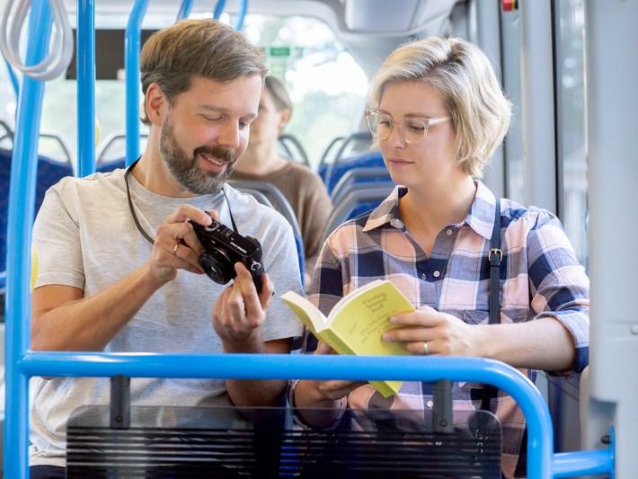 Kuvituskuva. Kolme ihmistä istuu bussissa.